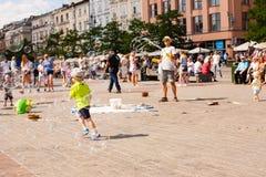 Jogo de crianças com bolhas de sabão na cidade velha Foto de Stock