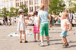 Jogo de crianças com bolhas de sabão na cidade velha Imagem de Stock Royalty Free