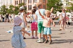 Jogo de crianças com bolhas de sabão na cidade velha Imagens de Stock