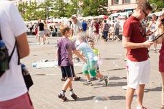 Jogo de crianças com bolhas de sabão na cidade velha Fotografia de Stock