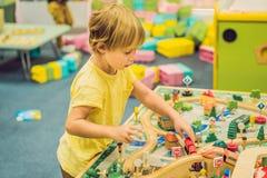 Jogo de crianças com brinquedo, a estrada de ferro do brinquedo da construção em casa ou guarda de madeira Jogo do menino da cria imagem de stock