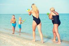 Jogo de crianças com minhas mãe e avó com as pistolas de água na praia Adultos novos imagens de stock royalty free