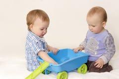 Jogo de crianças com o brinquedo no fundo branco Fotografia de Stock Royalty Free