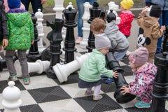Jogo de crianças com partes de xadrez gigantes em um grande tabuleiro de xadrez fotografia de stock