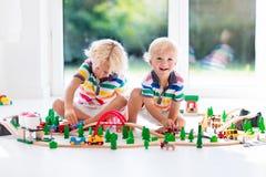 Jogo de crianças com trem do brinquedo Caçoa a estrada de ferro de madeira Imagem de Stock