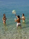 Jogo de crianças com uma esfera no mar Imagens de Stock