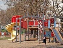 Jogo de crianças em um campo de jogos Foto de Stock