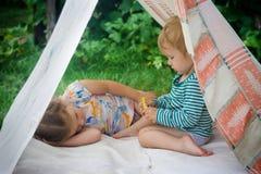 Jogo de crianças manchado na natureza em uma casa improvisada foto de stock