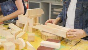 Jogo de crianças na oficina do ofício Rapaz pequeno bonito que joga com partes de madeira Tiro do close up Construção do menino 4 filme