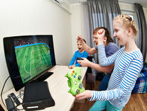 Jogo de crianças no console dos jogos para jogar o futebol Imagens de Stock Royalty Free