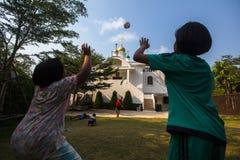 Jogo de crianças tailandês na bola perto da igreja ortodoxa do russo Imagem de Stock