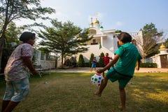 Jogo de crianças tailandês na bola perto da igreja ortodoxa do russo Foto de Stock