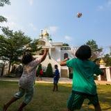 Jogo de crianças tailandês na bola perto da igreja ortodoxa do russo Imagens de Stock