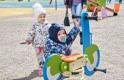 Jogo de crian?as pequeno no campo de jogos Desenvolvimento infantil jogos do ` s das crian?as Entretenimento para crian?as foto de stock