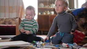 Jogo de dois meninos em casa com artigos de papelaria Os irmãos bonitos passam tempo interessante filme