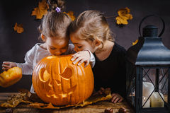 Jogo de duas meninas com uma abóbora de Dia das Bruxas Fotografia de Stock Royalty Free