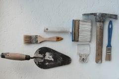 Jogo de facas de massa de vidraceiro Espátulas com o almofariz restante Gastarbeiter ou conceito do trabalhador imigrante imagens de stock royalty free