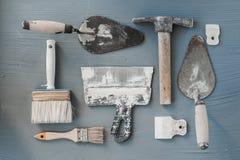 Jogo de facas de massa de vidraceiro Espátulas com o almofariz restante Gastarbeiter ou conceito do trabalhador imigrante imagem de stock