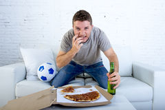 Jogo de futebol de observação do homem novo em unha cortante do sofrimento do esforço nervoso e entusiasmado da televisão no sofá imagens de stock