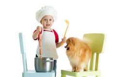 Jogo de interpretação de personagem O menino da criança joga o cozinheiro chefe com cão O cozinheiro weared criança alimenta o ca Fotos de Stock
