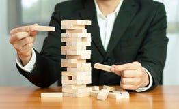 Jogo de negócio de Jenga, realização do negócio que constrói um estábulo falhado base da base do negócio do negócio e uma base in imagens de stock royalty free