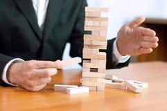 Jogo de negócio de Jenga, realização do negócio que constrói um estábulo falhado base da base do negócio do negócio e uma base in foto de stock