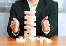Jogo de negócio de Jenga, realização do negócio que constrói um estábulo falhado base da base do negócio do negócio e uma base in imagem de stock royalty free