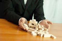 Jogo de negócio de Jenga, realização do negócio que constrói um estábulo falhado base da base do negócio do negócio e uma base in fotos de stock royalty free