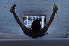 Jogo de observação sozinho do futebol ou de futebol da casa do homem novo na televisão que aprecia e que comemora o objetivo Fotografia de Stock