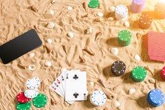 Jogo de pôquer em linha na praia com esperto digital e as pilhas de microplaquetas Vista superior Imagens de Stock