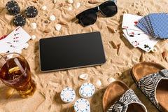 Jogo de pôquer em linha na praia com tabuleta e as pilhas digitais de microplaquetas Vista superior Imagem de Stock Royalty Free