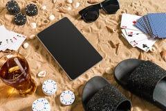 Jogo de pôquer em linha na praia com tabuleta e as pilhas digitais de microplaquetas Vista superior Imagem de Stock