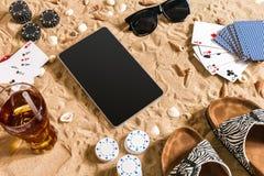 Jogo de pôquer em linha na praia com tabuleta e as pilhas digitais de microplaquetas Vista superior Foto de Stock Royalty Free