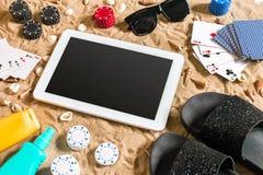 Jogo de pôquer em linha na praia com tabuleta e as pilhas digitais de microplaquetas Vista superior Fotos de Stock