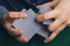 Jogo de pôquer nas mãos do ` s dos homens na tabela verde Imagem de Stock