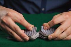 Jogo de pôquer nas mãos do ` s dos homens na tabela verde Fotografia de Stock