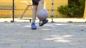 Jogo de pernas de um menino novo com uma bola em um passo do futebol da rua video estoque