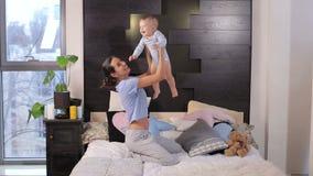Jogo de sorriso da mamã nova feliz com seu filho pequeno do bebê que encontra-se na cama em casa filme