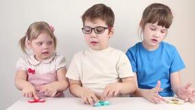 Jogo de três crianças feliz com giradores vídeos de arquivo