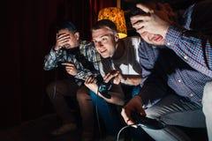 Jogo de vídeo emocional do jogo de três indivíduos, competição Imagens de Stock Royalty Free