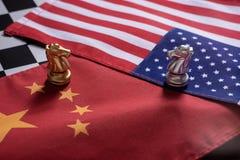 Jogo de xadrez, dois cavaleiros cara a cara em China e bandeiras nacionais dos E.U. Conceito da guerra comercial Conflito entre d fotos de stock royalty free