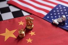 Jogo de xadrez, dois cavaleiros cara a cara em China e bandeiras nacionais dos E.U. Conceito da guerra comercial Conflito entre d imagens de stock