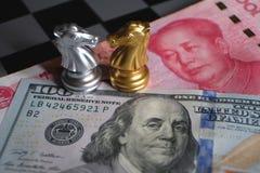 Jogo de xadrez, dois cavaleiros cara a cara no fundo chinês do yuan e do dólar americano Conceito de comércio da maneira Conflito fotos de stock