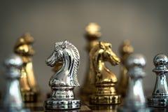 Jogo de xadrez Um suporte do cavaleiro determinadamente entre os inimigos Conceito competitivo do neg?cio imagens de stock