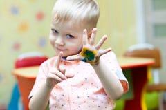 Jogo do bebê e suas mãos cobertos com as cores brilhantes imagens de stock