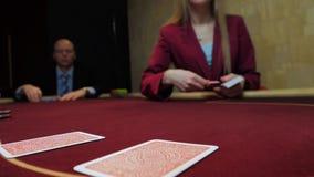 Jogo do casino: O negociante negocia os cartões Aposta dos jogadores Carda o close-up Movimento lento video estoque