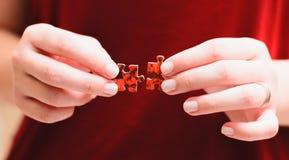 Jogo do enigma de serra de vaivém: Mãos de uma mulher que guarda e que combina dois pi Foto de Stock
