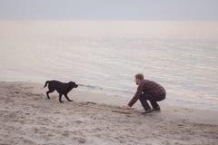 Jogo do homem com cão Fotos de Stock Royalty Free