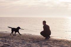 Jogo do homem com cão Fotografia de Stock Royalty Free