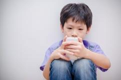 Jogo do jogo do menino no telefone esperto fotografia de stock